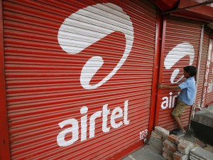A boy closes shutter of shop painted with advertisement for Bharti Airtel in Ahmedabad
